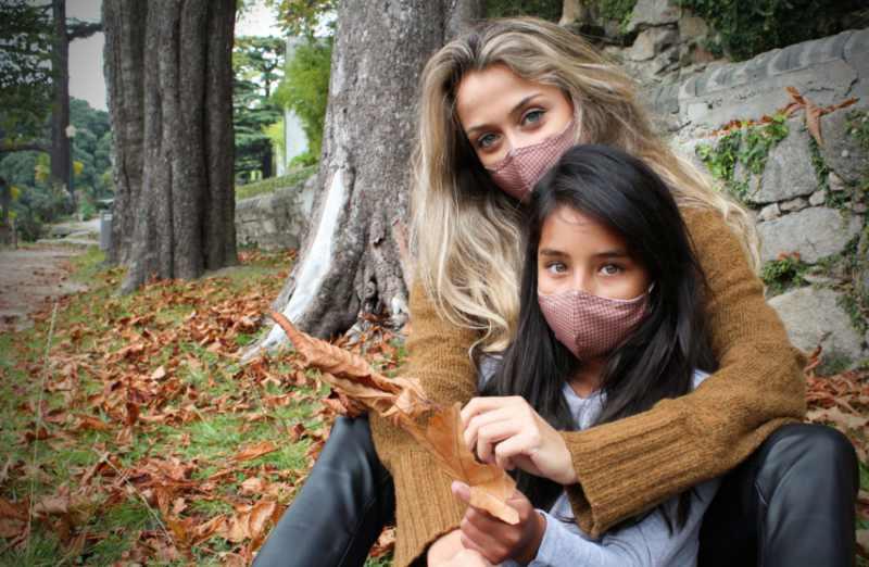 Masken bedrucken lassen Mutter mit Kind beide tragen eine Maske im Hintergrund herbstlicher Park